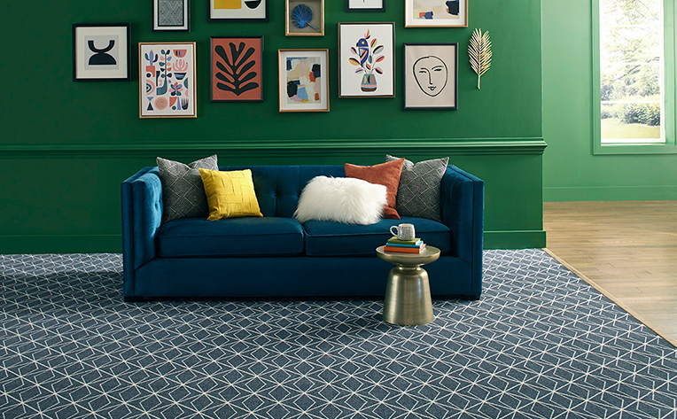 Blue patterned flooring in living room with green gallery walls